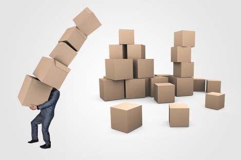 Businessman carrying a pile of moving boxes.