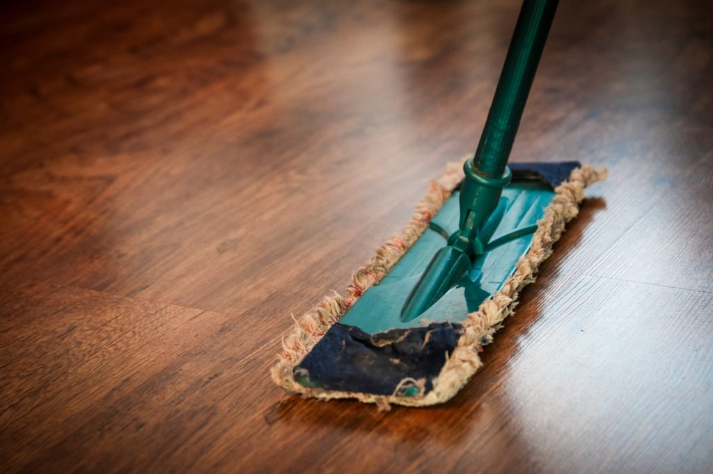 Cleaning your apartment on moving day by mopping the floors.