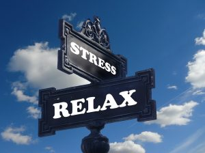 "A ""Stress"" sign on top of a""Relax"" sign, blue sky with white clouds in the background"