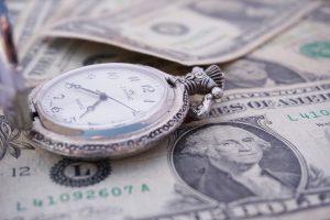 A pocket watch lying on dollar bills