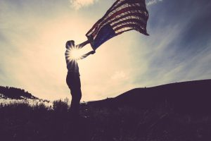 A man's silhouette holding the American flag, the sky in the background
