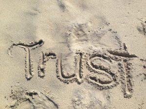 "The word ""Trust"" written in sand"