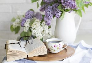 A book with reading glasses, cup of coffee and flowers