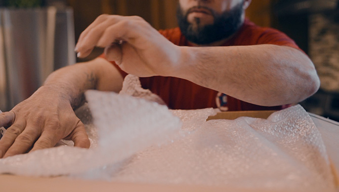 A local moving professional using bubble wrap to protect valuable items