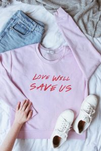a pink shirt, white sneakers and jeans