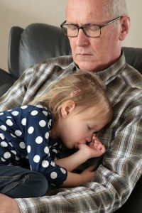 grandchild and grandfather asleep