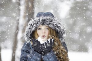 A woman blowing snow out of her hands.