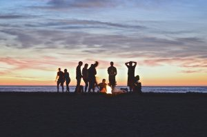 A group of people on the beach trying to organize a farewell party.