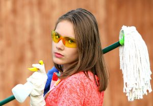 A girl holding a mop and cleaning supplies.