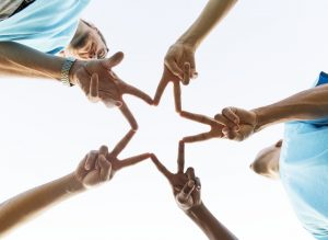 A group of people forming a star with their hands.