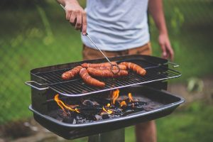 Man using his barbecue before packing home grill for relocation.