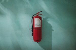 red fire extinguisher on a green wall to prevent in-home fire hazards