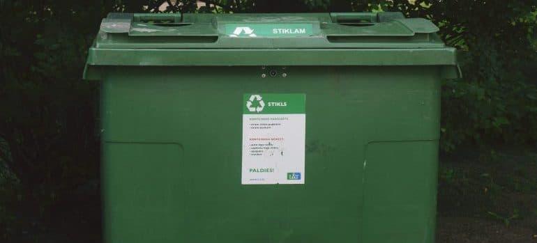 a green plastic dumpster